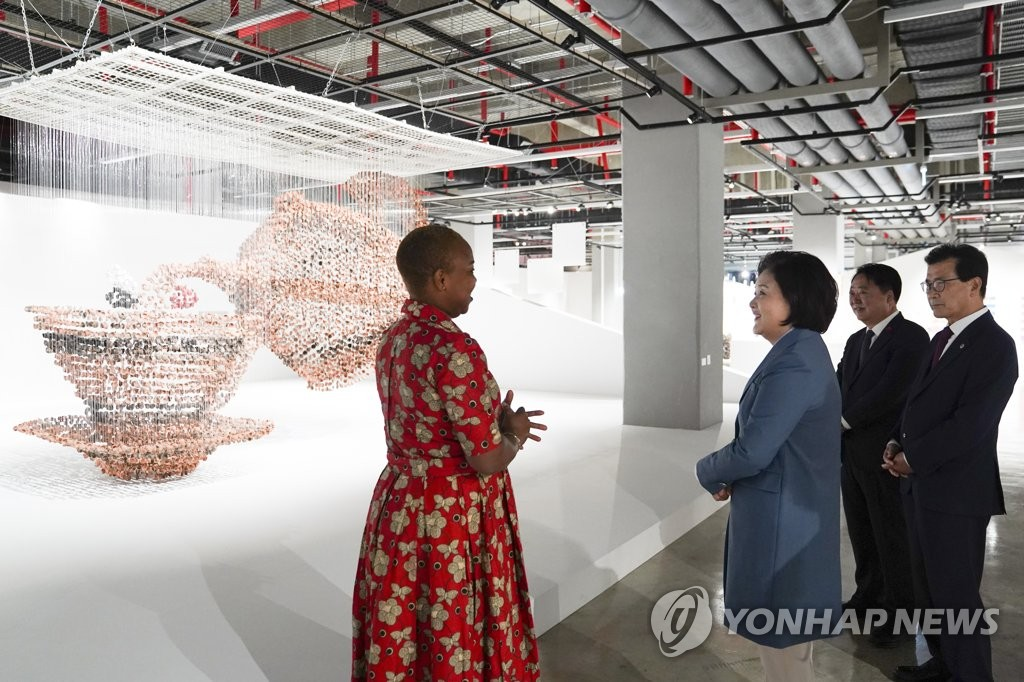 First lady Kim Jung-sook (2nd from L) listens to a craft artist explaining her work at the Cheongju Craft Biennale in the central city of Cheongju on Oct. 7, 2019. (Yonhap)