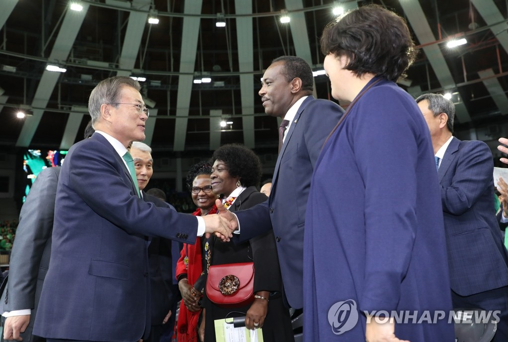 President Moon Jae-in shakes hands with a foreign envoy attending an annual conference on the Saemaul movement held at a gymnasium in Suwon, Gyeonggi Province, on Oct. 29, 2019. (Yonhap)