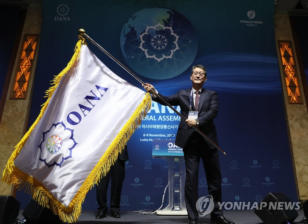Yonhap News Agency CEO Cho Sung-boo waves a flag after Yonhap is elected as the new chair for the Organization of Asia-Pacific News Agencies (OANA) at its 17th General Assembly held at Lotte Hotel Seoul in Seoul on Nov. 8, 2019. (Yonhap)