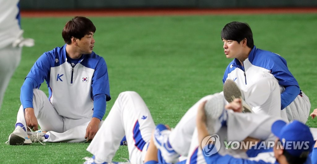 South Korean pitcher Kim Kwang-hyun (L) and outfielder Min Byung-hun chat as they stretch before their practice at Tokyo Dome in Tokyo on Nov. 14, 2019, the eve of a game against Mexico in the Super Round at the World Baseball Softball Confederation (WBSC) Premier12. (Yonhap)
