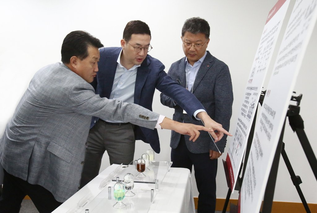 This photo, provided by LG Group on Dec. 20, 2019, shows LG Group chief Koo Kwang-mo (C) speaking with officials from LG Chem Ltd. during a visit to the company's research facility in Daejeon. (PHOTO NOT FOR SALE) (Yonhap)