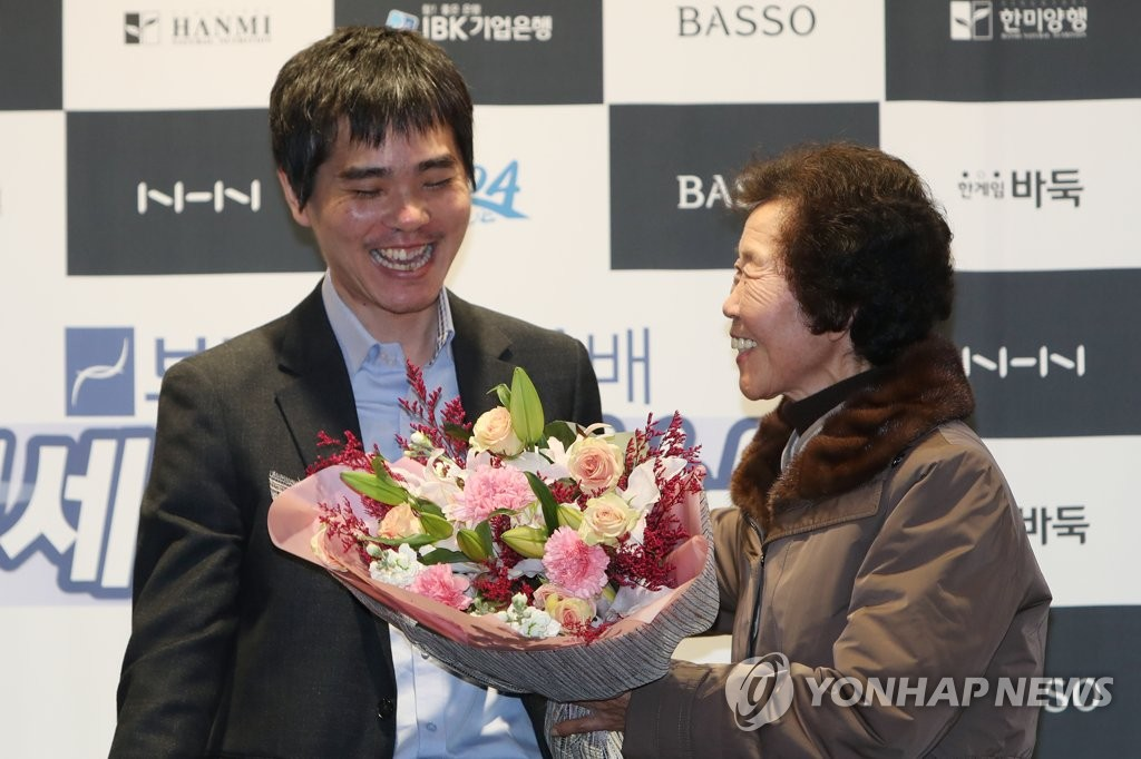 South Korean Go player Lee Se-dol (L) receives a bouquet of flowers from his mother, Park Yang-rye, after his retirement match against artificial intelligence program HanDol at El Dorado Resort in Sinan, 400 kilometers south of Seoul, on Dec. 21, 2019. (Yonhap)