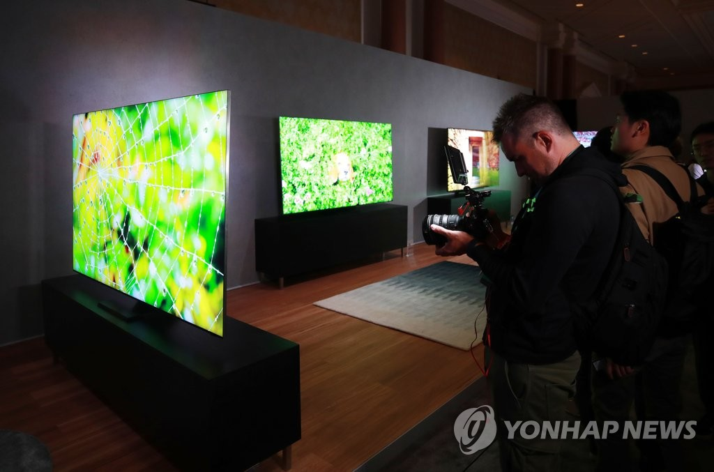 A group of reporters look at Samsung Electronics Co.'s new QLED 8K TV products at the Samsung TV First Look 2020 event in Las Vegas, Nevada, on Jan. 5, 2020, two days ahead of the Consumer Electronics Show. (Yonhap)