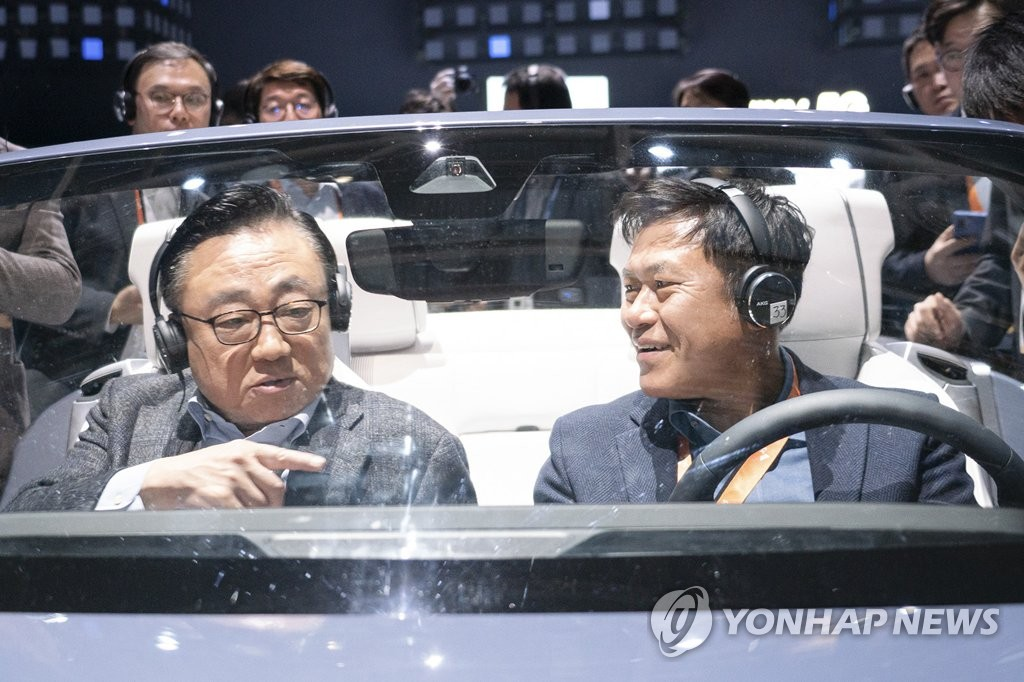 In this photo provided by SK Telecom Co. on Jan. 7, 2020, SK Telecom CEO Park Jung-ho (R) speaks with Koh Dong-jin, president and CEO of Samsung Electronics' mobile business division, at a digital cockpit made by Samsung at the company's Consumer Electronics Show (CES) booth in Las Vegas, Nevada. (PHOTO NOT FOR SALE) (Yonhap)