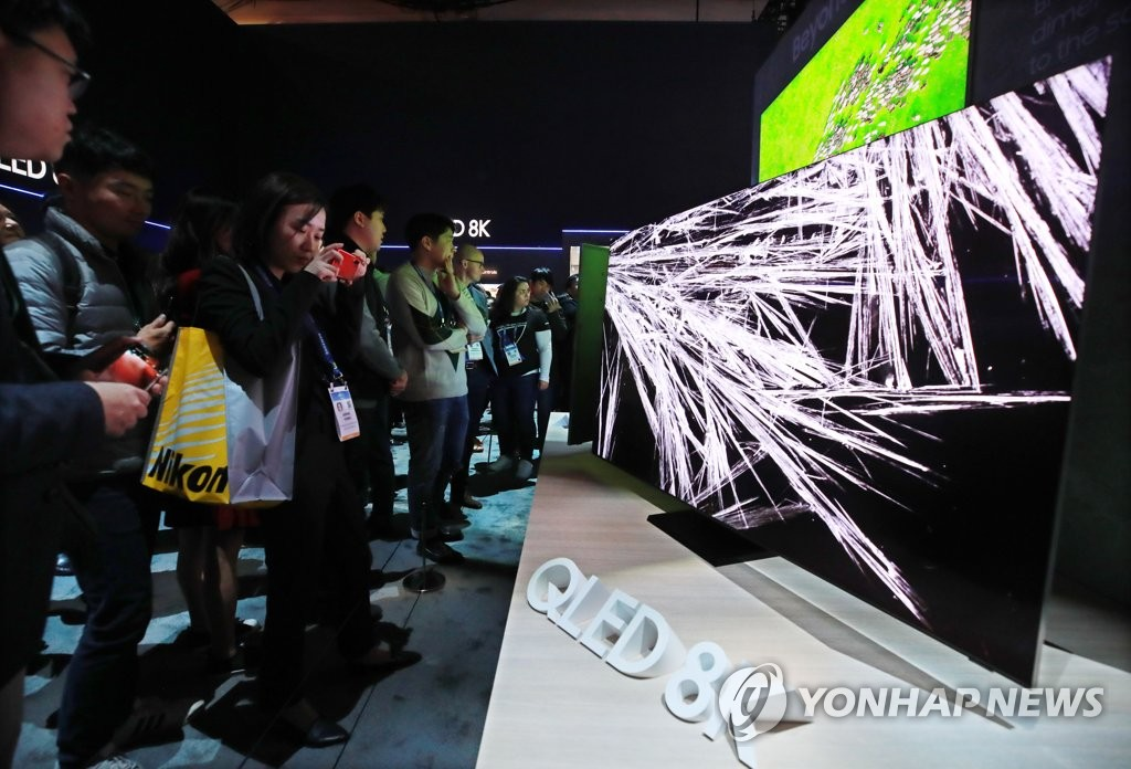 This photo taken on Jan. 8, 2020, shows people looking at Samsung Electronics Co.'s QLED 8K TVs at the company's exhibition booth at the Consumer Electronics Show in Las Vegas, Nevada. (Yonhap)