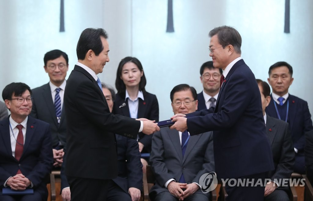 President Moon Jae-in (R) hands a letter of appointment over to Prime Minister Chung Sye-kyun during a Cheong Wa Dae ceremony on Jan. 14, 2020. (Yonhap)
