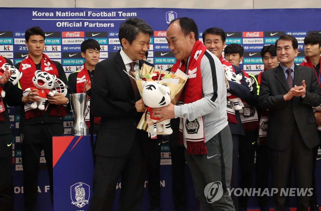Kim Hak-bum (R), head coach of the South Korean men's Olympic football team, receives a bouquet of flowers from Korea Football Association President Chung Mong-gyu at Incheon International Airport, just west of Seoul, on Jan. 28, 2020, after returning from winning the Asian Football Confederation (AFC) U-23 Championship in Thailand. (Yonhap)