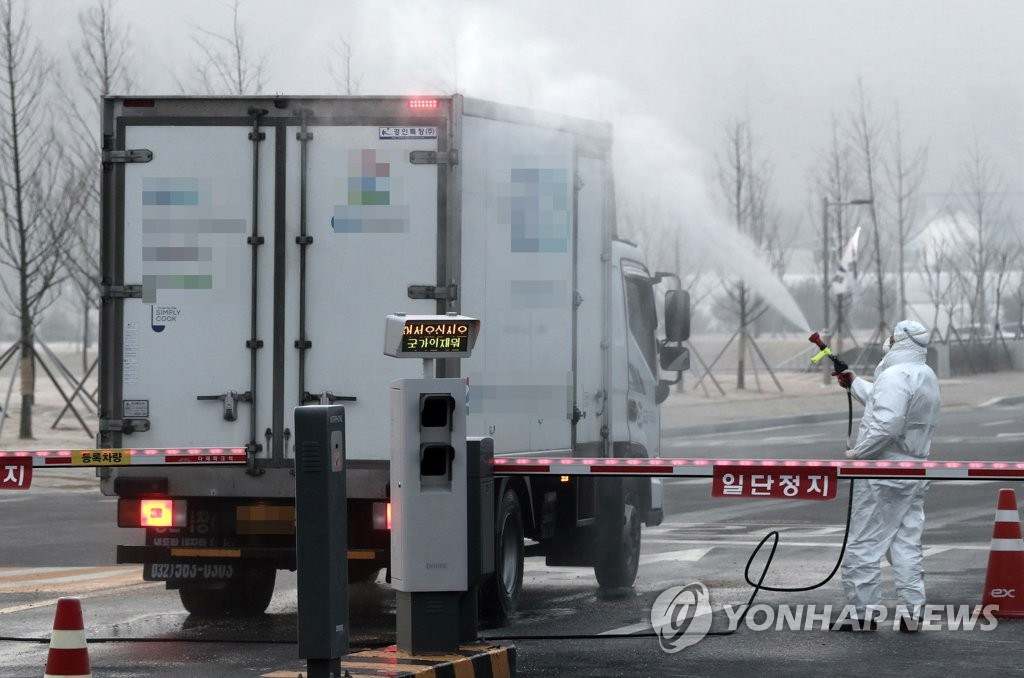 A truck carrying lunch boxes for South Korean evacuees from Wuhan, China, is being disinfected before entering their shelter in Jincheon, 90 kilometers southeast of Seoul, on Feb. 2, 2020. (Yonhap)