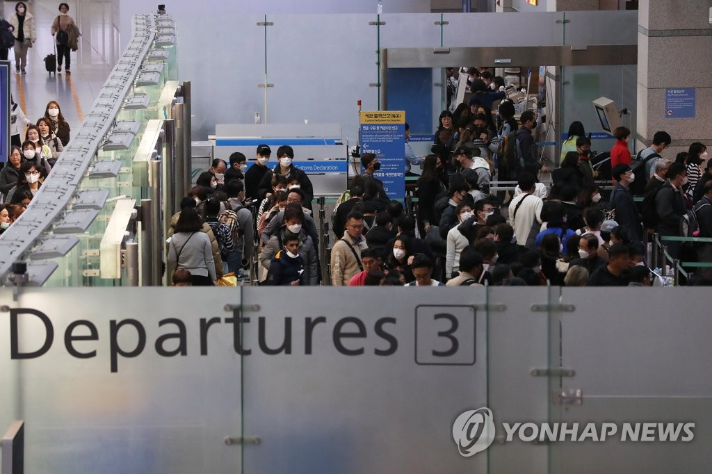 Travelers line up in a queue at Terminal 2 of Incheon International Airport on Feb. 2, 2020. (Yonhap)