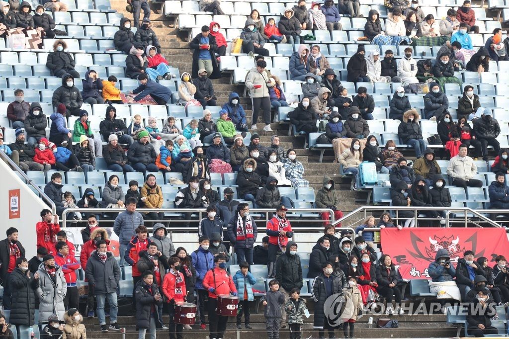 This file photo, from Feb. 9, 2020, shows fans wearing masks in the stands at Jeju World Cup Stadium in Seogwipo, Jeju Island, during an Olympic women's football qualifying match between the home team South Korea and Vietnam. (Yonhap)