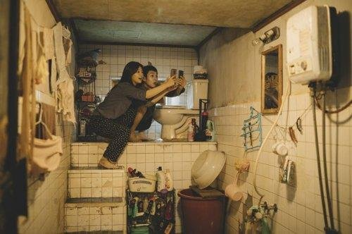 "This image, provided by CJ Entertainment, shows the fictional Kim siblings searching for a WiFi signal at their half-basement flat in the film ""Parasite."" (PHOTO NOT FOR SALE) (Yonhap)"