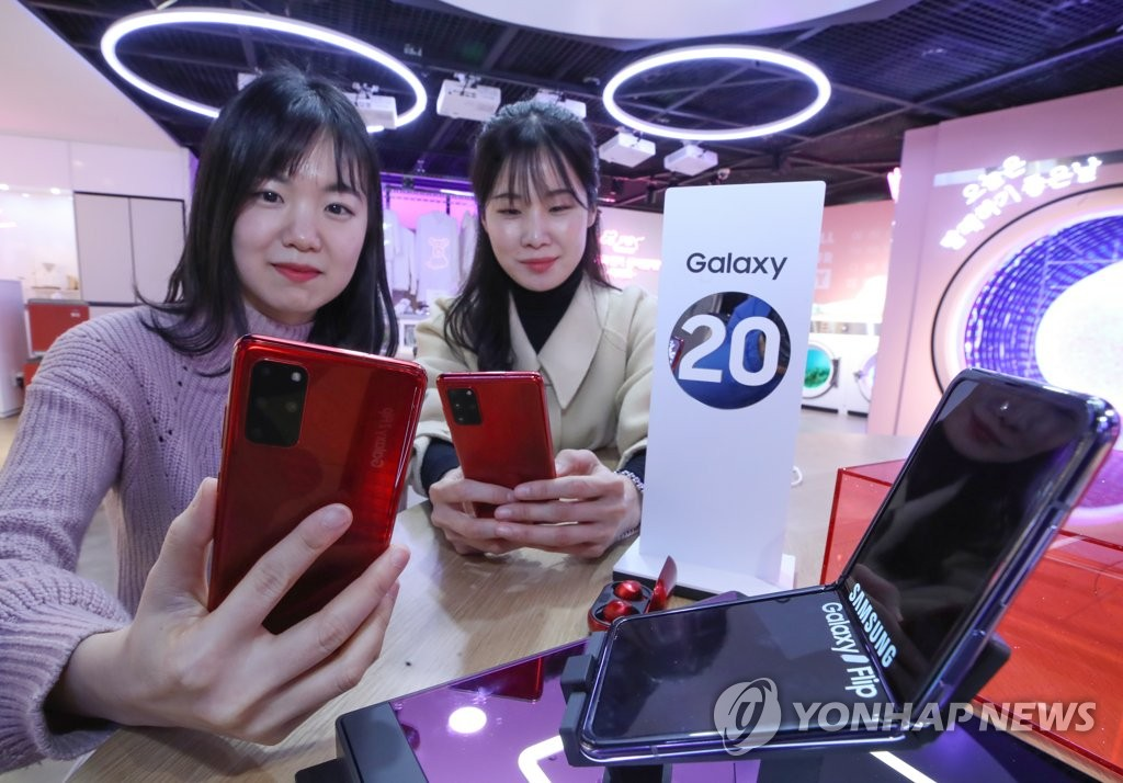 In this photo taken on Feb. 12, 2020, models present Samsung Electronics Co.'s Galaxy Z Fold (front, R) and Galaxy S20 smartphones at a store in Seoul. (Yonhap)