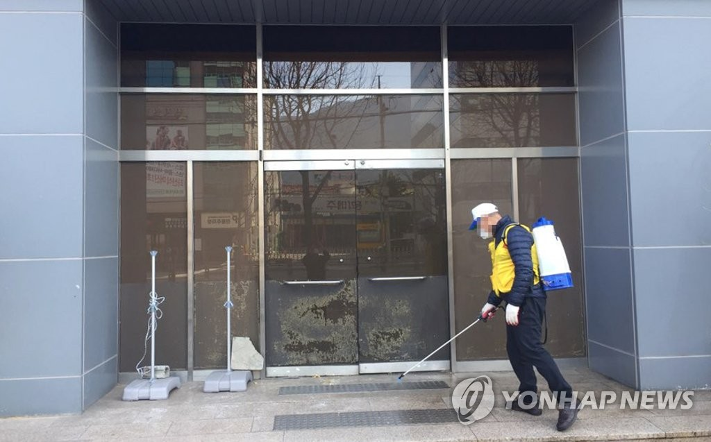 A quarantine official disinfects the building of a Shincheonji church in Daegu on Feb. 23, 2020. (Yonhap)