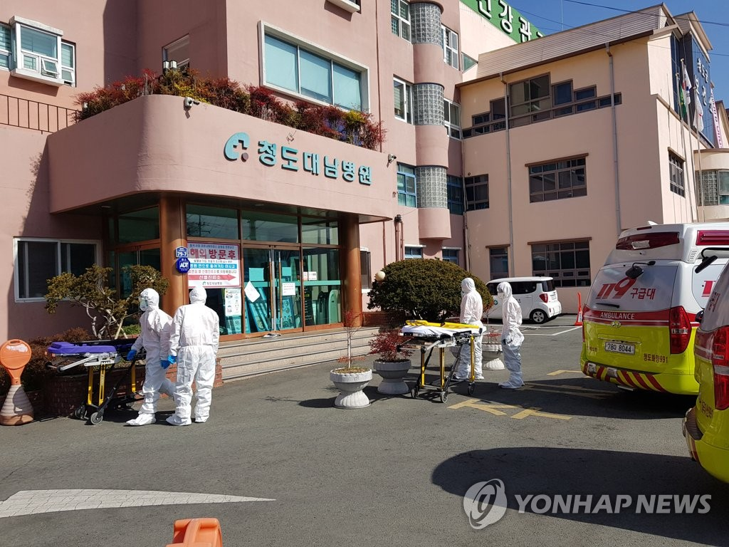 In this photo taken Feb. 24, 2020, medical workers prepare to transport a COVID-19 patient from Daenam Hospital in Cheongdo, 300 kilometers southeast of Seoul, which has so far reported the infections of 112 patients and medical staff. (Yonhap)