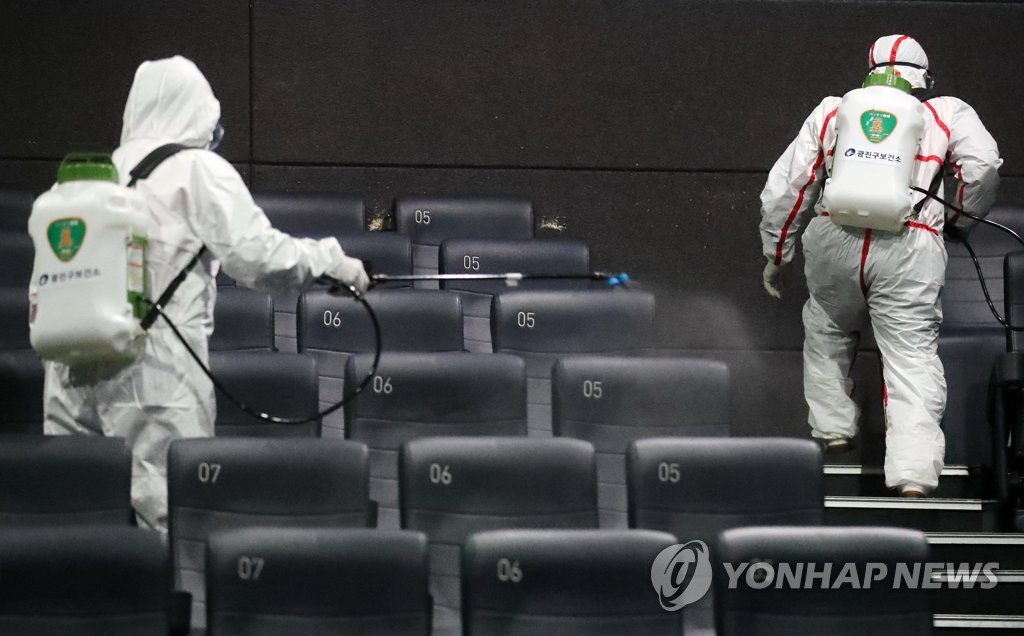 In this photo taken Feb. 26, 2020, quarantine officials disinfect a movie theater in Seoul known to have been visited by a person diagnosed with the new coronavirus, COVID-19. (Yonhap)