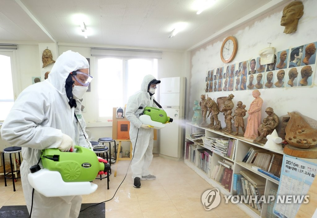 Health workers disinfect a private sector art class in the southern port city of Busan on March 6, 2020. (Yonhap)