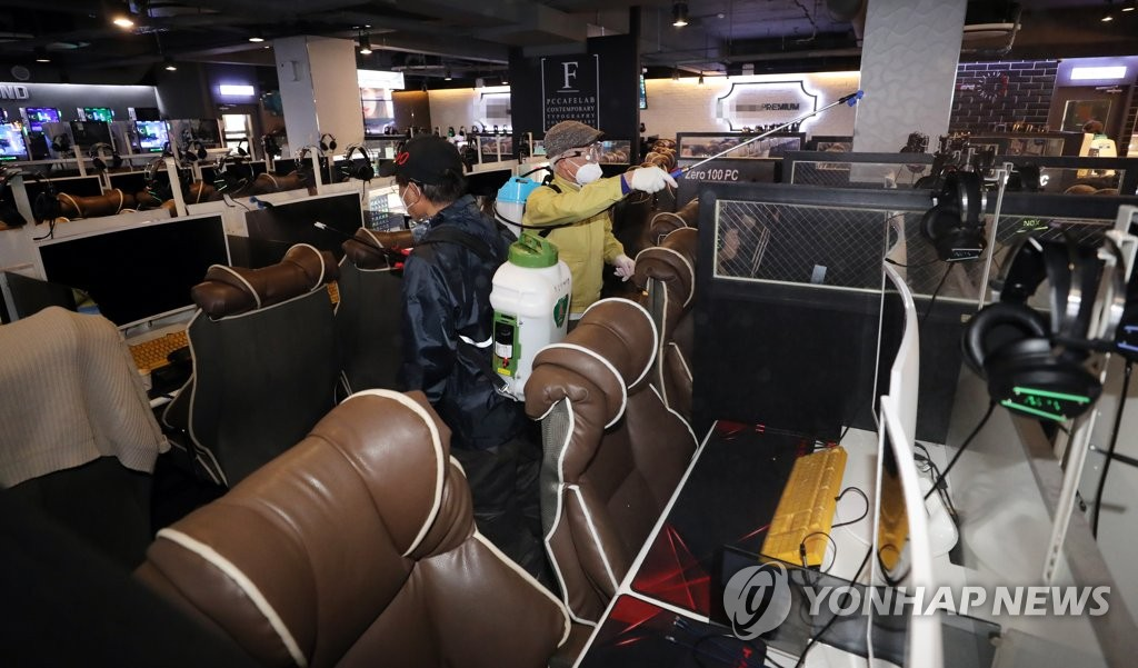 Health officials disinfect an internet cafe in Seongdong Ward in eastern Seoul on March 12, 2020. (Yonhap)