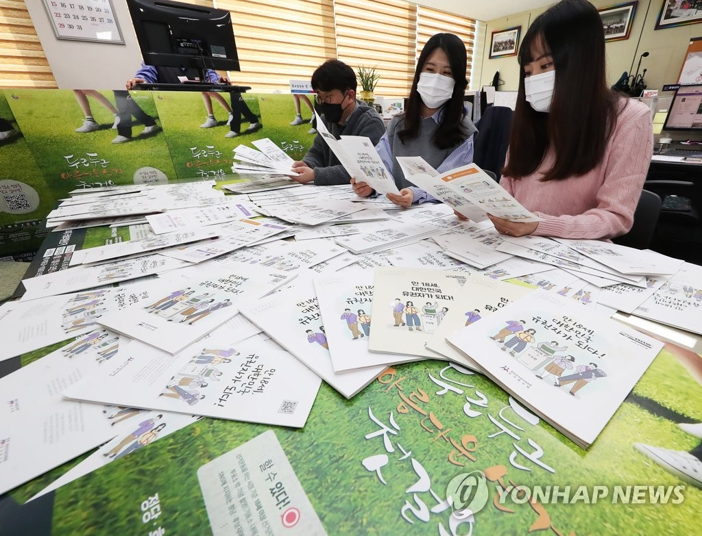 Officials at the National Election Commission look at election education materials for 18-year-old high school student voters in Suwon, south of Seoul, on March 24, 2020. (Yonhap)