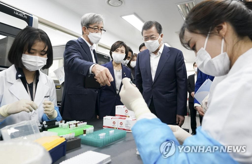 South Korean President Moon Jae-in (C) watches researchers at Seegene Inc. test COVID-19 diagnostic reagents at the company's research facility in Seoul on March 25, 2020. (Yonhap)