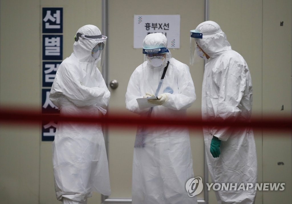 Los miembros del personal médico, vestidos con equipamiento de protección sanitaria, realizan preparativos frente a una instalación para las pruebas del nuevo coronavirus, el 26 de marzo de 2020, en un hospital en la ciudad de Daegu, azotada por el coronavirus.
