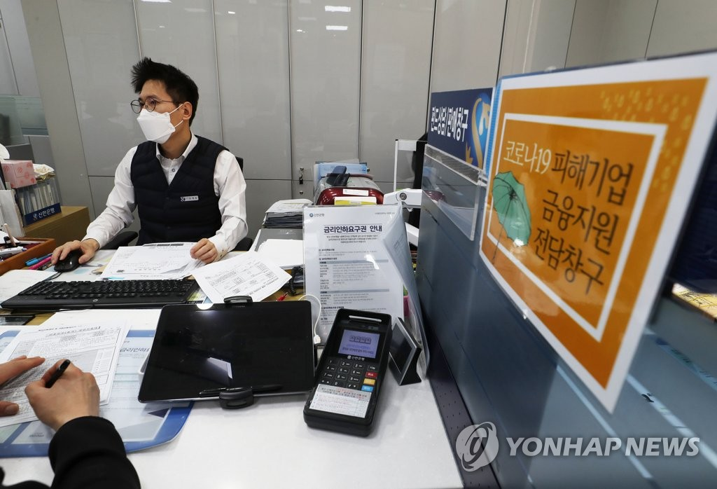 In this file photo, taken on April 1, 2020, a bank official at Shinhan Bank in Seoul holds an interview with a customer seeking a special low-interest loan for small and medium-sized firms hit by the new coronavirus outbreak. (Yonhap)