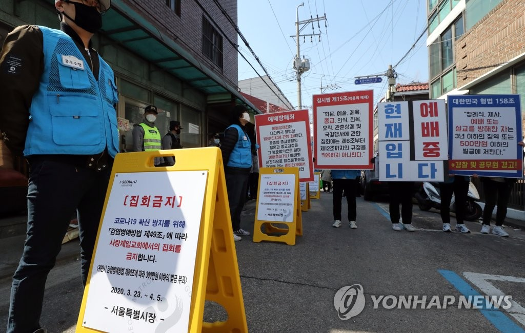 Followers of Sarang Jeil Church hold up signs detailing laws that guarantee their religious freedom, as the Seoul-based church goes ahead with its Sunday service on April 5, 2020, despite the city's administrative order not to hold mass gatherings to prevent the spread of the coronavirus. (Yonhap)