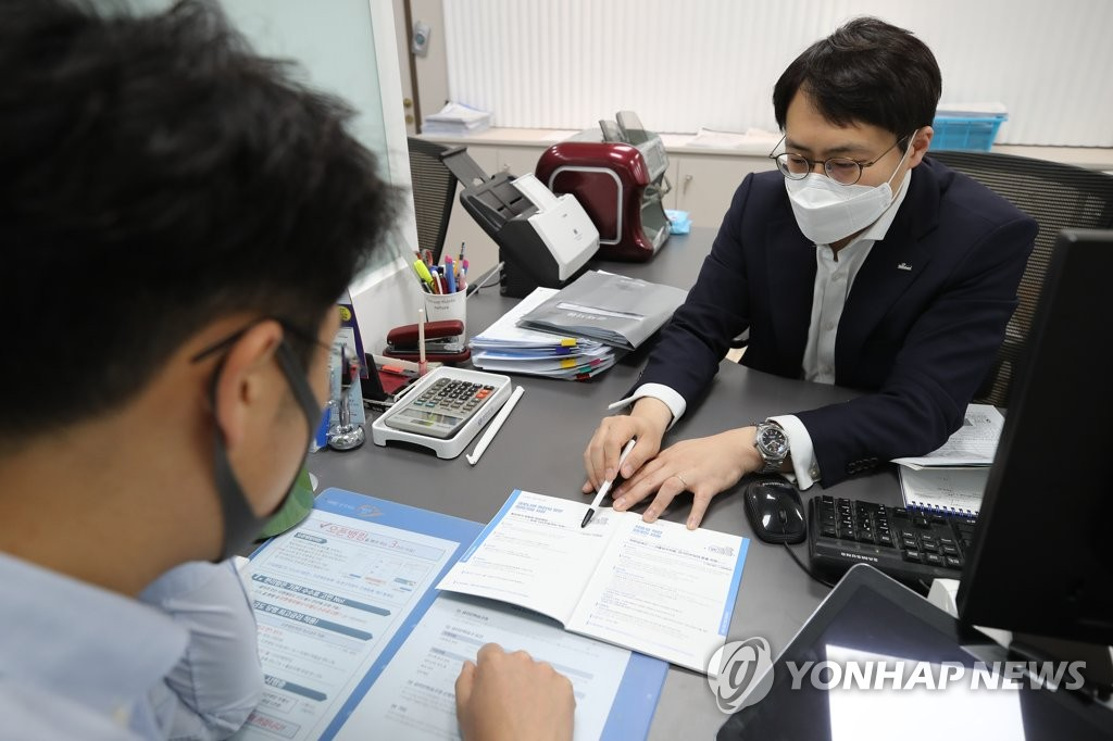 In the photo, taken April 6, 2020, a local customer (L) is seen holding an interview with a bank official in Seoul for a special, low-interest loan for businesses hit by the COVID-19 pandemic. (Yonhap)