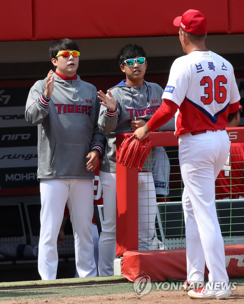 In this file photo from April 7, 2020, Aaron Brooks of the Kia Tigers (R) is greeted by teammates Yang Hyeon-jong (L) and Im Gi-yeong after the top of the fifth inning of an intrasquad game at Gwangju-Kia Champions Field in Gwangju, 330 kilometers south of Seoul. (Yonhap)