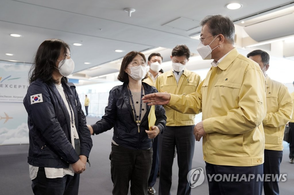 President Moon Jae-in (R) talks with a quarantine official at Incheon International Airport, west of Seoul, on April 7, 2020 in this photo provided by Cheong Wa Dae. (PHOTO NOT FOR SALE) (Yonhap)