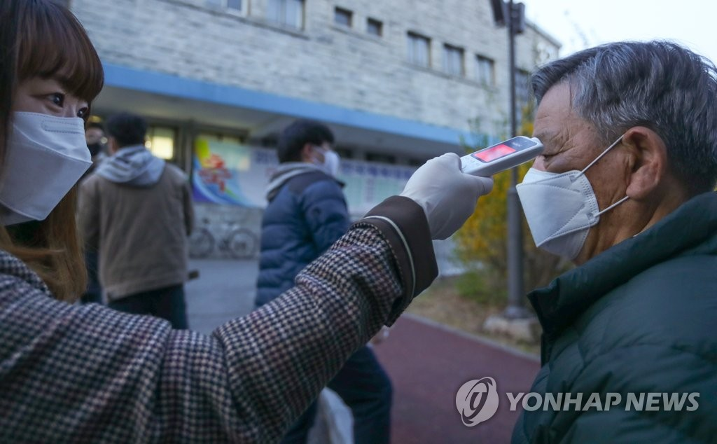 An official checks a voter's temperature at a polling station in the southern city of Gongju on April 10, 2020. (Yonhap)