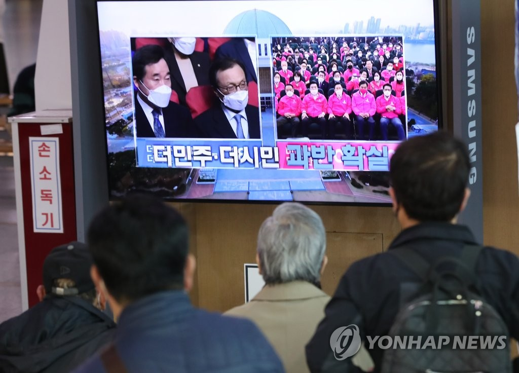 In this file photo taken April 15, 2020, citizens watch a television news report on the results of the 21st parliamentary elections at Seoul Station in the capital city. (Yonhap)