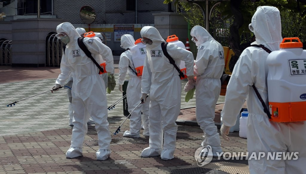 Military officials carry out a disinfection operation at an elementary school in Daegu, located 300 kilometers south of Seoul, on April 21, 2020. (Yonhap)