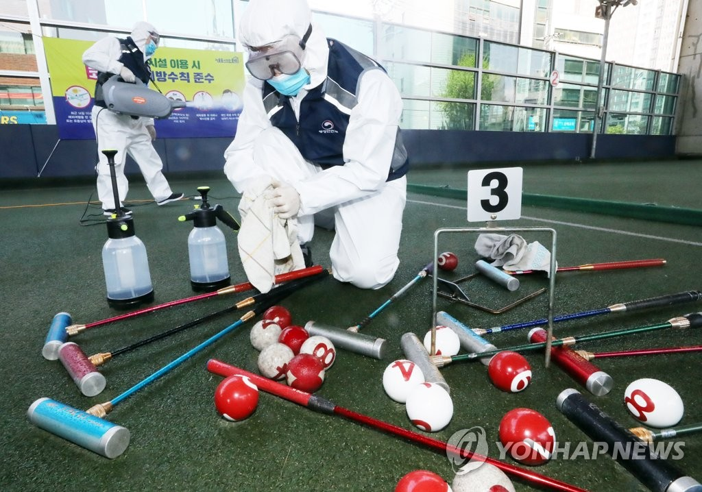 Quarantine officials disinfect tools at a sports facility located in southern Seoul on April 23, 2020, to prepare for its reopening after an almost two-month suspension due to the spread of the new coronavirus. (Yonhap)