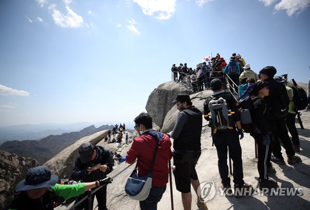 The Baekwundae peak on Mount Bukhan in Seoul is crowded with hikers on April 26, 2020, the first Sunday since the government eased its social distancing rules amid a slowdown in new coronavirus cases. (Yonhap)