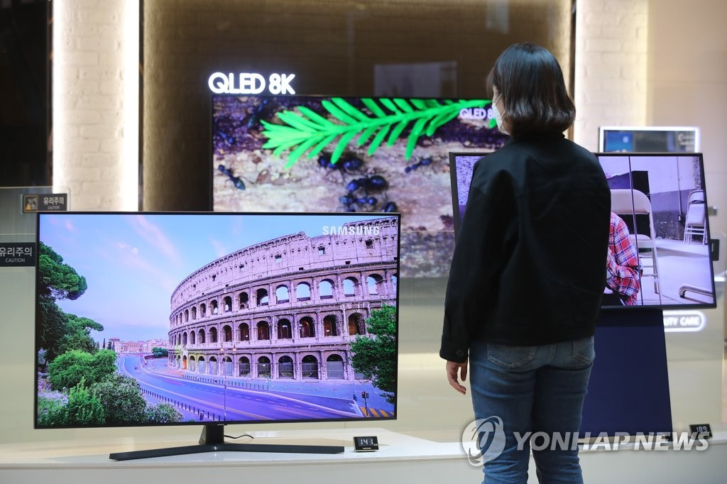 This file photo taken April 29, 2020, shows a customer looking at Samsung Electronics Co.'s QLED TVs at a store in Seoul. (Yonhap)