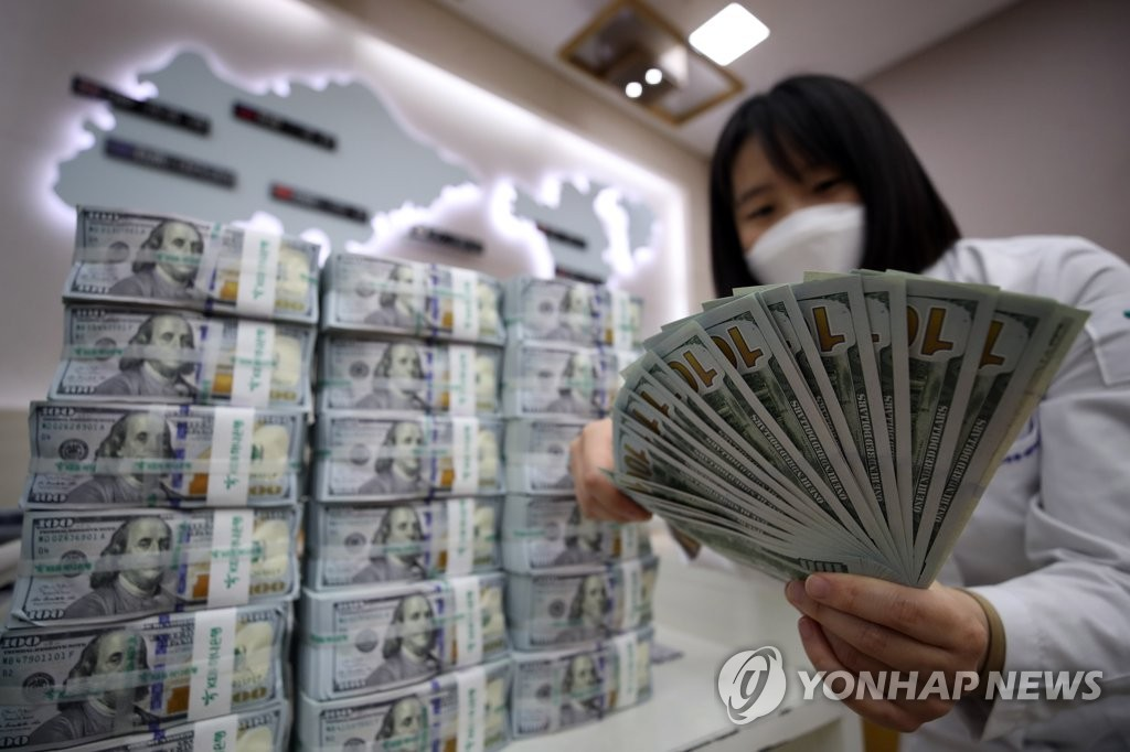 In the undated file photo, a bank official checks U.S. banknotes for counterfeits at a bank in Seoul. (Yonhap)