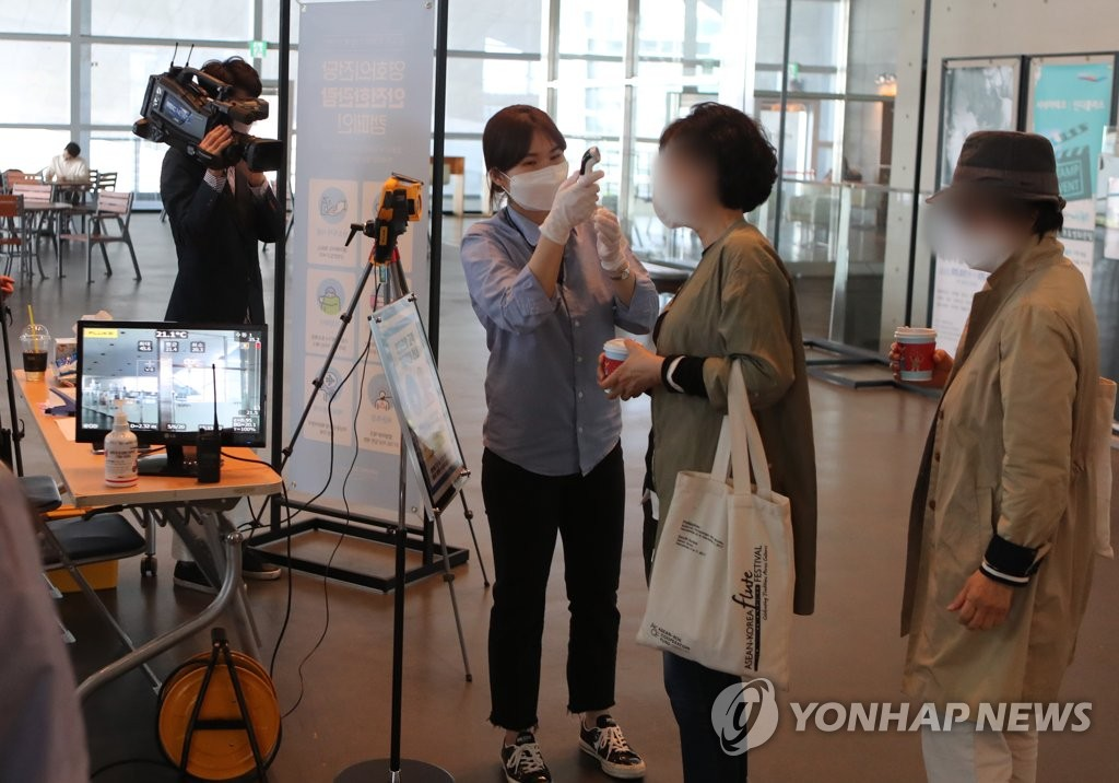 The file photo from May 6, 2020, shows people having their temperature checked at a movie theater in Busan. (Yonhap)