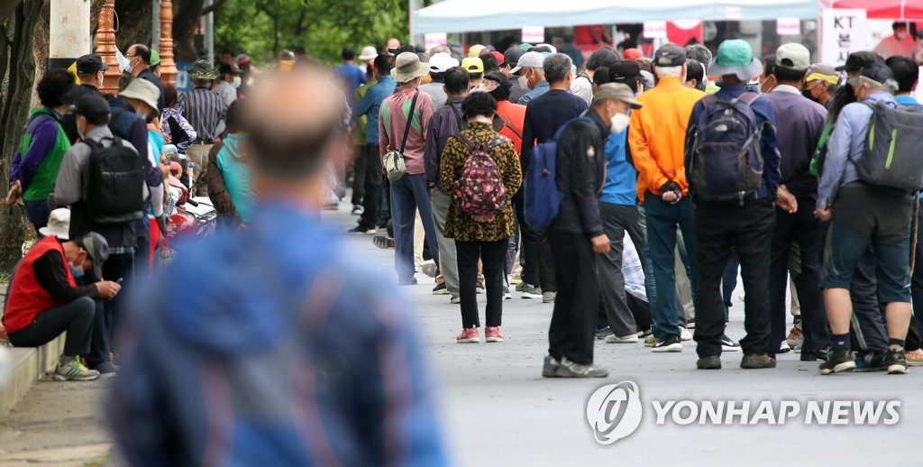 This file photo shows people waiting in line to eat at a free meal station in Daegu, 302 kilometers south of Seoul, on May 14, 2020. (Yonhap)