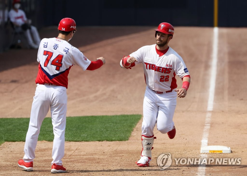 Preston Tucker of the Kia Tigers (R) bumps fists with his third base coach Kim Jong-gook after hitting a solo home run against the Doosan Bears in a Korea Baseball Organization regular season game at Gwangju-Kia Champions Field in Gwangju, 330 kilometers south of Seoul, on May 17, 2020. (Yonhap)