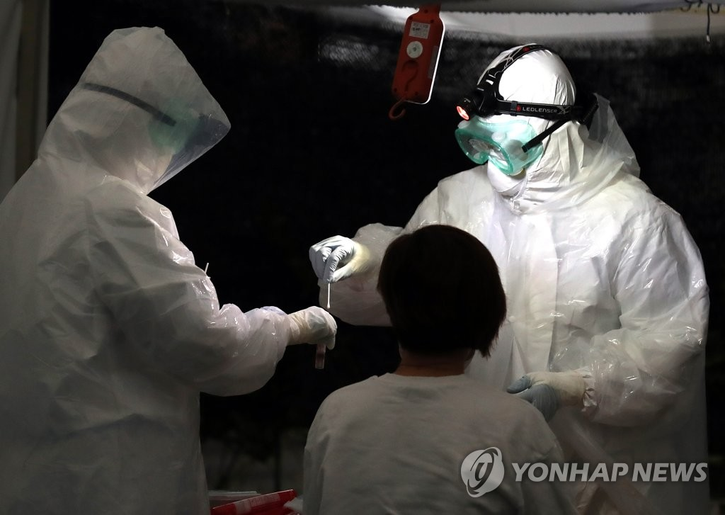 Health workers conduct a virus screening test at a community health center in Bucheon, just outside of Seoul, on May 18, 2020. (Yonhap)