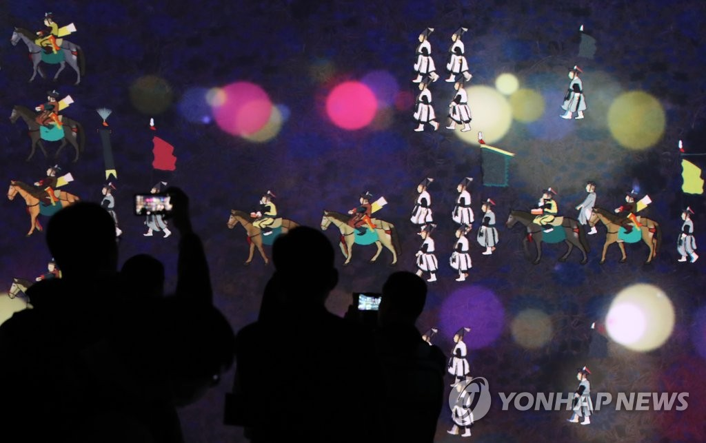In this file photo, spectators watch the changing of colorful images projected onto a panoramic screen that is part of the Immersive Digital Gallery during its opening event held at the National Museum of Korea in Seoul on May 19, 2020. (Yonhap)