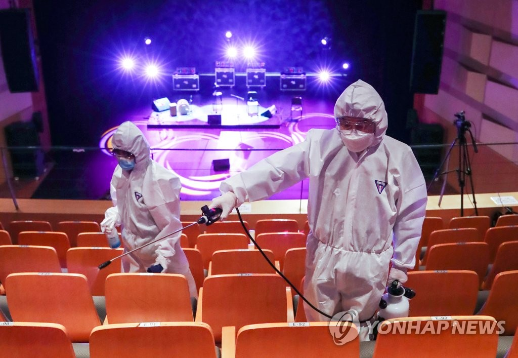 Building management workers carry out disinfection operations at a concert hall located in western Seoul on May 21, 2020. (Yonhap)