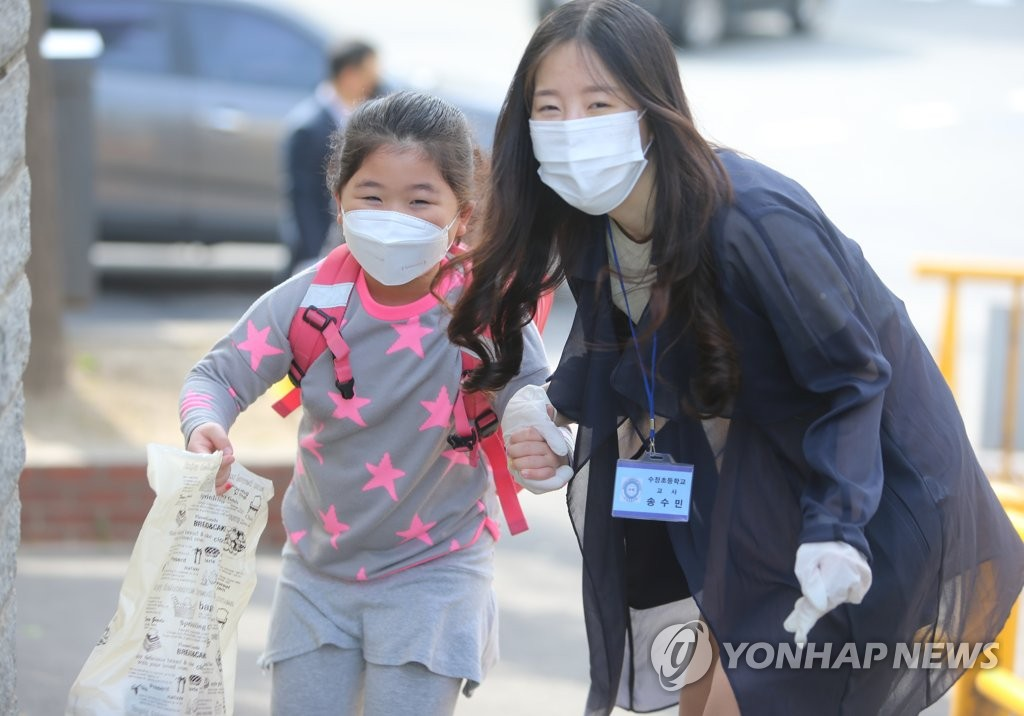 A teacher holds the hand of her student at an elementary school in the southern port city of Busan on May 27, 2020. (Yonhap)