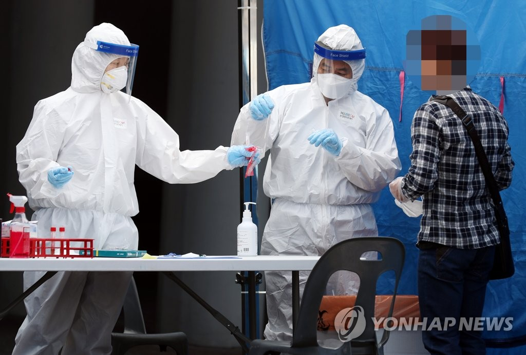 Health workers conduct a coronavirus test on a citizen at an outdoor testing center in Bucheon, west of Seoul on May 27, 2020 as the country reported a steady rise in logistics center-tied cases. (Yonhap)