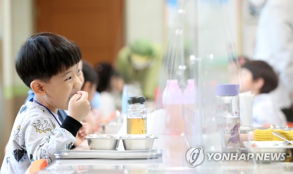An elementary school student eats lunch at a table equipped with plastic barriers to prevent spread of the new coronavirus at a cafeteria in Chuncheon, 85 kilometers east of Seoul, on May 27, 2020. (Yonhap)
