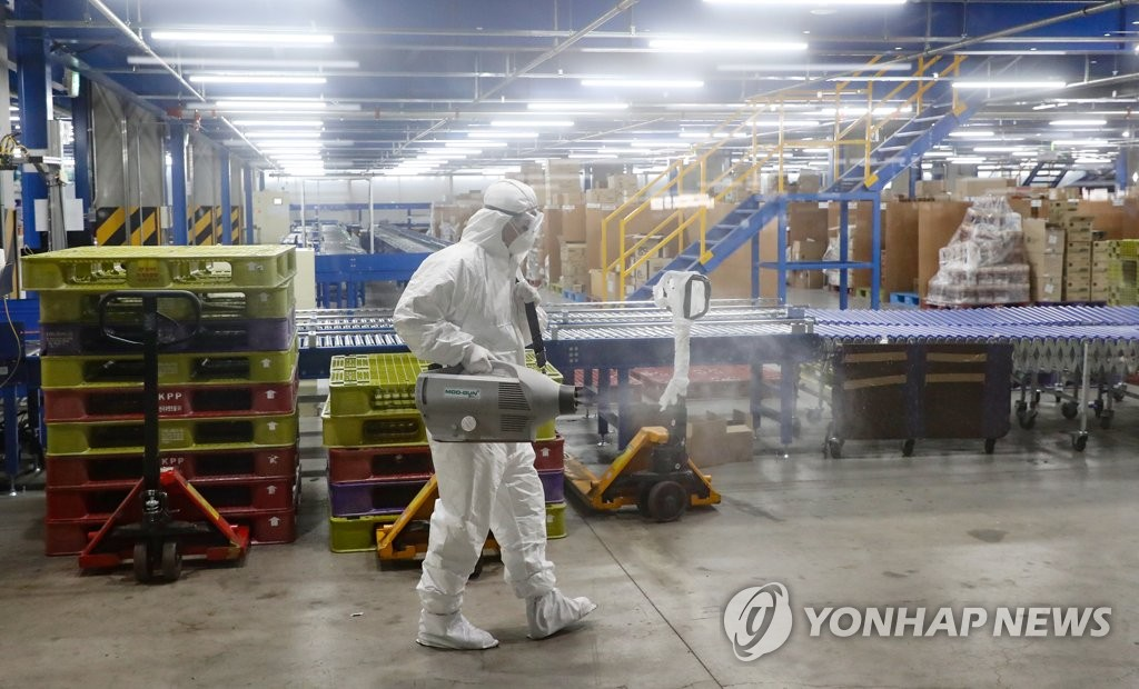 A worker disinfects a logistics center of Market Kurly, an online grocery delivery platform, in eastern Seoul on May 27, 2020. (Yonhap)