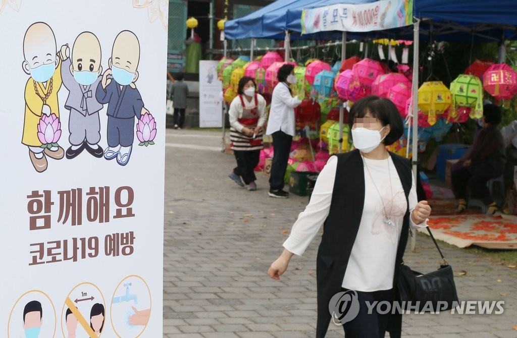 A mask-wearing visitor attends a ceremony marking Buddha's Birthday at a temple on the southern resort island of Jeju on May 30, 2020. (Yonhap)
