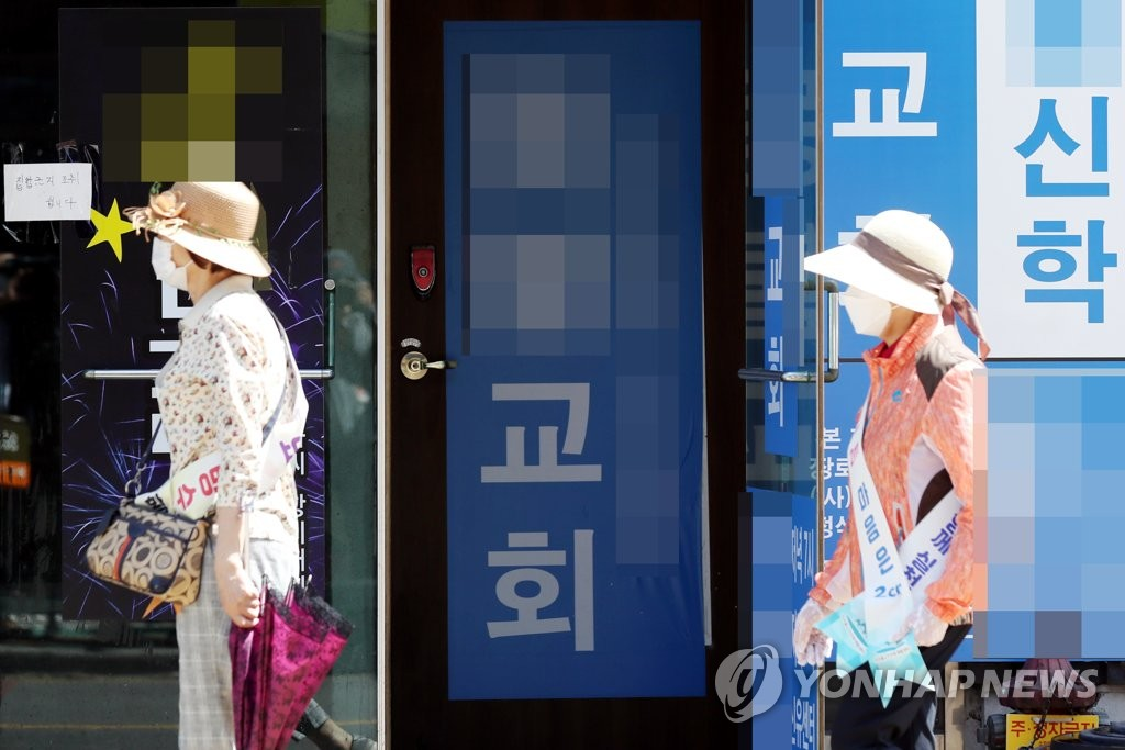 Campaigners promoting quarantine guidelines walk past a church in Incheon, west of Seoul, on June 1, 2020, following group infections reported at the religious facility. (Yonhap)