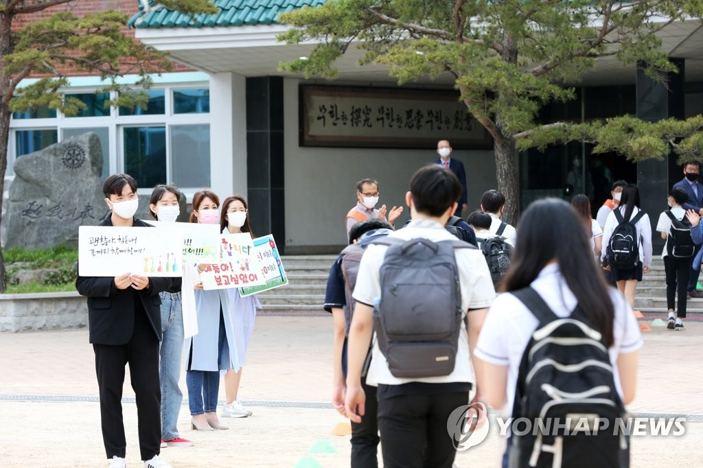 Teachers hold signs welcoming students at a high school in the southern port city of Pohang, 374 kilometers south of Seoul, on June 3, 2020. (Yonhap)