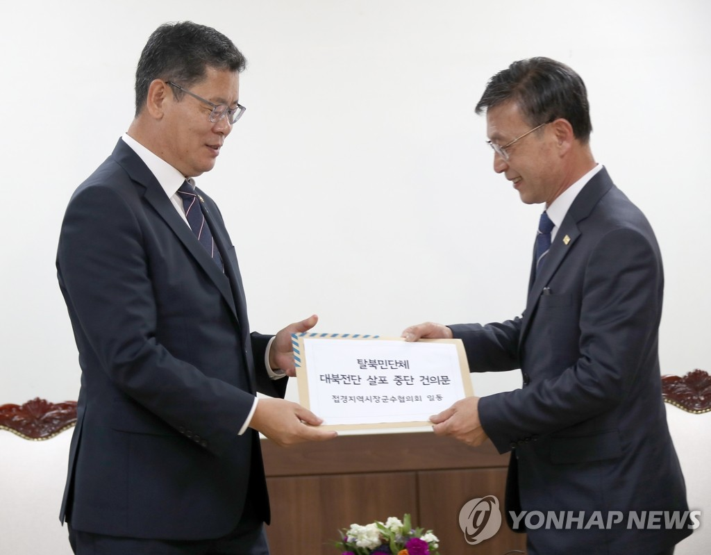 Unification Minister Kim Yeon-chul (L) receives a letter from Jung Ha-young, mayor of Gimpo, calling for stricter regulations to stop defector groups from flying leaflets into North Korea, on June 5, 2020. (Yonhap)